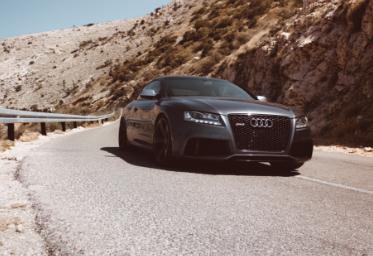 Black Audi driving on a desert road